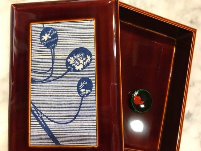 蓋に「長板中形」の生地がはめ込まれている伝統工芸品の「飛騨春慶」の小物入れ