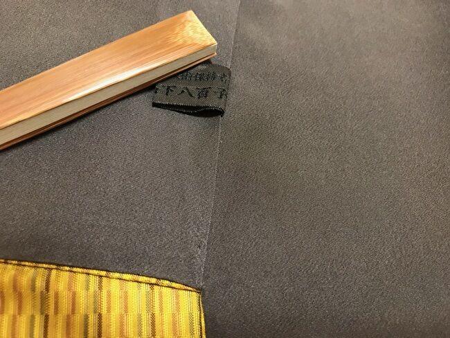 「黄八丈めゆ工房」の山下八百子の黄八丈の着物・八掛の色は山下八百子の証紙の色と同じ焦げ茶色